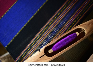 Close up of spool with purple thread in wooden local equipment for weaving fabric in traditional Thai style