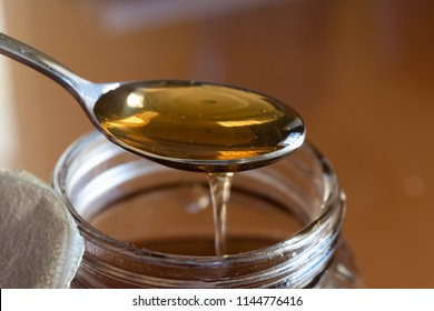 Close up of a spoonful of delicious shiny organic natural unrefined honey dripping of spoon into an open jar of golden honey for natural sweetener and healthy eating concept