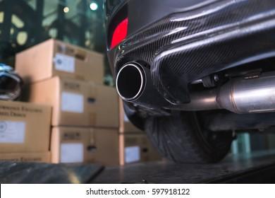 Close up sport car carbon fiber exhaust pipe in garage