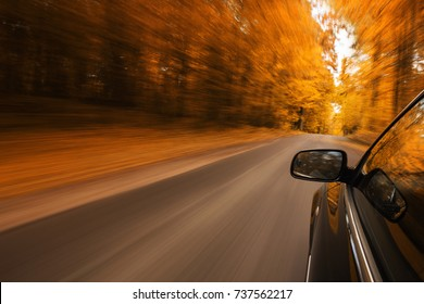 Close up of a sport car speeding on the empty, autumn road with copy space