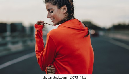 Close up of a sportswoman in tracksuit standing outdoors. Woman taking break on after a morning run.