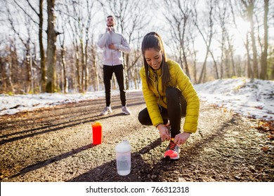Close up of sporty active beautiful smiling slim woman in sportswear kneeling on the road and tying shoelaces in the sunny winter morning outside in nature with a handsome trainer behind her.