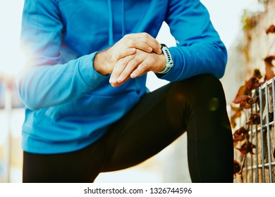 Close up of sporty bearded man kneeling and setting stopwatch. Healthy lifestyle concept.