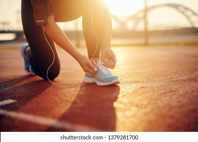 Close up of sporty caucasian woman kneeling and tying shoelace on court in the morning. Every mile you hit your mind will want to give up.