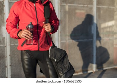 Close up of sporty man holding bottle of water before urban outdoor workout.
