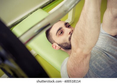 Close up of sporty man lift weights at the gym
