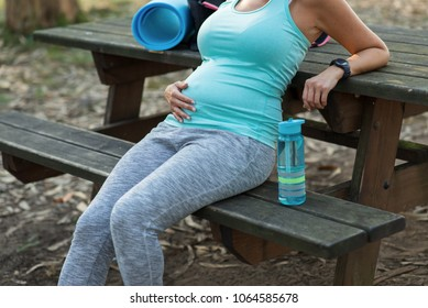 Close up of sporty pregnant woman belly taking a rest during outdoor healthy fitness workout. Expectant healthy mother taking a break.