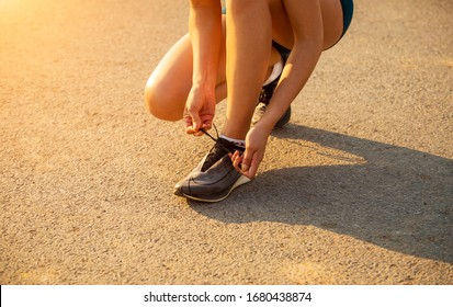 Close up of sporty woman tying shoelace on asphalt road in the morning