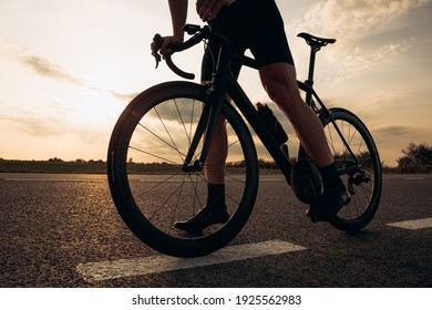 Close up of sporty young man with strong legs standing on road with black bike. Natural landscape, evening time. Cycling concept.