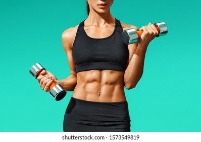 Close up of sporty young woman with muscular body on turquoise background with copy space. Sports and healthy lifestyle