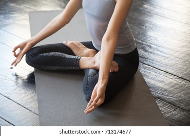 Close up of sporty young woman practicing yoga, sitting in Lotus exercise, Padmasana pose with mudra, working out wearing sportswear, studio floor background. Wellbeing and wellness concept