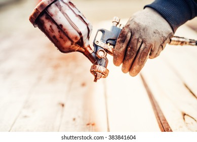 Close up of a spray paint gun and worker hand