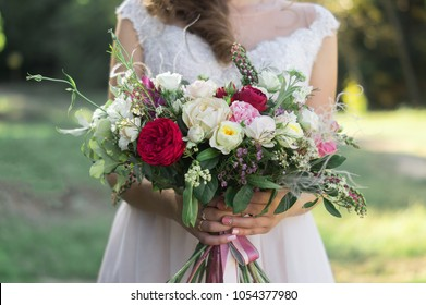 Close up of spring wedding bouquet of burgundy roses, pink eustomas, field flowers and green leaves