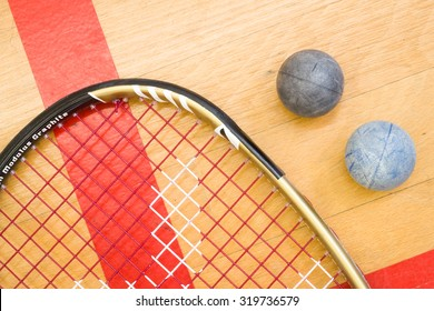 Close up of a squash racket and ball on the wooden background