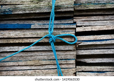 Close up of a stack of chipboard tiles bound together with a blue nylon rope with a knot