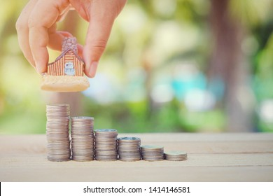 close up stack of coin on table, hand holding toy house, green nature copy space background for text, saving money for future, manage to success building business technology concept