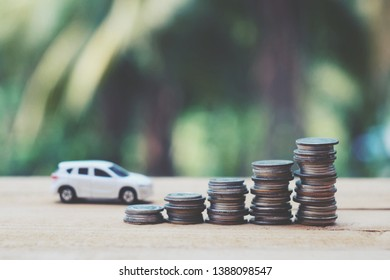 close up stack of coin and toy car onold wood table, green nature copy space background for text, saving money for future, manage to success transport business technology concept