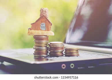 close up stack of coin and toy house on notebook, saving money for building, manage to success, property business technology concept, vintage tone