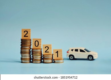 close up stack of coin, wooden 2021 text block and toy car on blue background, saving and manage money for new year season, transport insurance technology, economic crisi risk and problem concept
