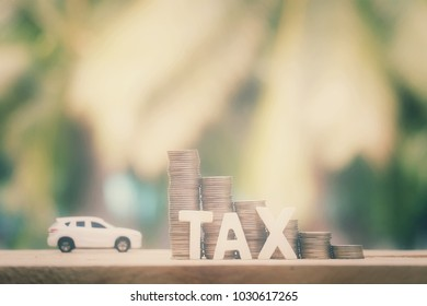 close up stack of coins and tax wooden text on old woid table with toy car background, saving money for transport, manage for success business, vintage tone