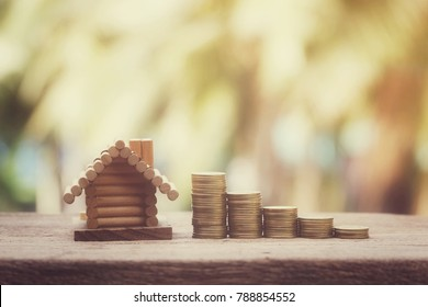 close up stack of coins and toy wooden house on old wood table with nature copy space background for text, saving money for building and manage for success business concept, process vintage tone