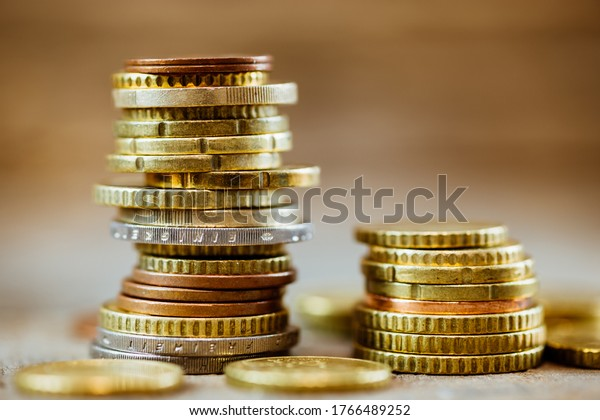 Close up stack of euro coins on a rustic wooden table