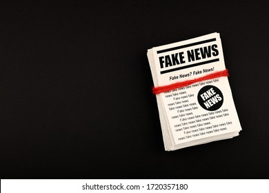 Close up stack of FAKE NEWS newspapers over black paper background with copy space, elevated top view, directly above
