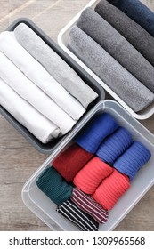 Close up stack of folded t shirt black gray white color and folded bright colorful socks in plastic baskets on wooden floor background in natural light. Room cleaning and tidying up concept.