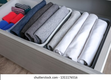 Close up stack of folded t shirt black gray white color and folded bright colorful socks in plastic baskets in a closet drawer in natural light. Room cleaning and tidying up concept. Top view.