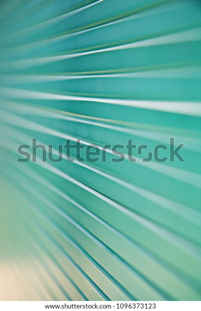 Close up of a stack of green glass panels with converging lines and shallow depth of field.