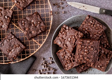 Close up of stack of keto chocolate chip brownies on gray stoneware plate with additional brownies on copper baking rack with knife on the side