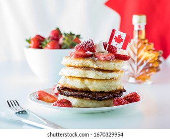 A close up of a stack of pancakes and strawberries for Canada Day with a maple leaf bottle of syrup. Canada Day concept.