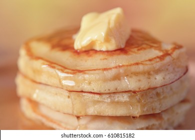 close up Stack of pancakes in syrup and butter dessert on dish at wood table. selective focus