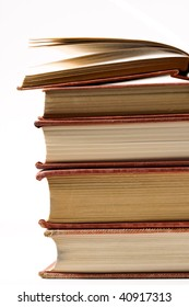 Close up of stack of very old, well worn books with shallow depth of field