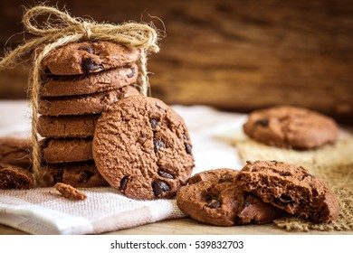Close up stacked chocolate chip cookies on  napkin with wooden background