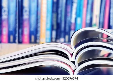 close up stacking of opened magazine with blurry bookshelf background , extremely shallow DOF