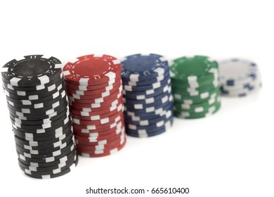 Close up of stacks of different coloured gaming chips isolated against a white background