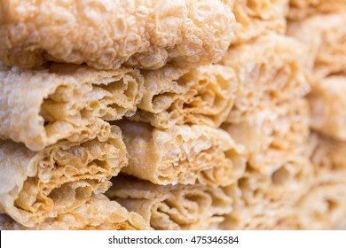 Close up of stacks of roll up fried tofu skins or bean curd, selective focus with shallow depth of field, showing texture of fried tofu skin