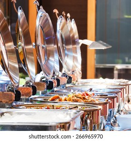 Close up stainless steel countertop food warmer and dish on table, catering concept