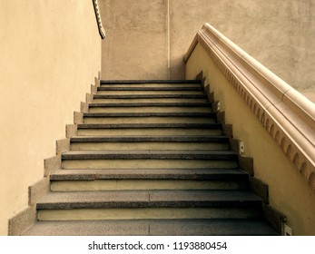 Close up of a staircase with old, rustic look. Concrete flights going up with vintage looking railing. Architectural details.