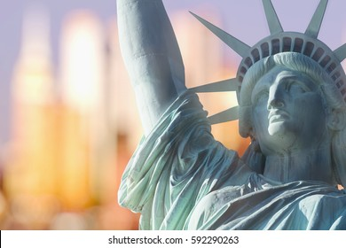 CLOSE UP STATUE OF LIBERTY WITH BOKEH BACKGROUND OF SKYSCRAPERS IN MANHATTAN, NEW YORK, USA