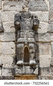 Close up of the statue of a Mayan god with head missing standing on the outside of a building on the ancient site of Kabah