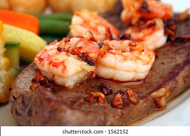 Close up of a steak with garlic butter sauce and fresh king prawns - surf n' turf