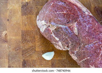 A close up of the steak with marinating sauce and garlic.