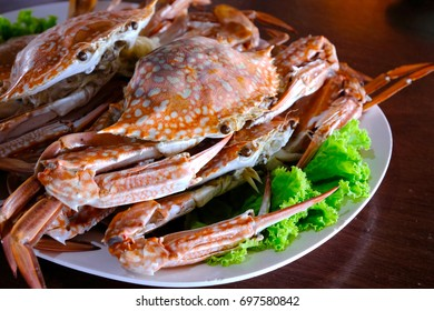 Close up steamed blue crab with green lettuce under served in the plate in Thai seafood restaurant