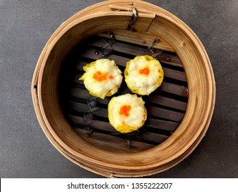 Close up steaming Chicken Shumai (Shaomai, Siumaai) top with small fish eggs in bamboo steamer served as a dim sum snack for breakfast is delicious Chinese dumpling in traditional Cantonese cuisine