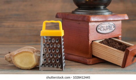 Close up of steel grater and ginger root on wooden background