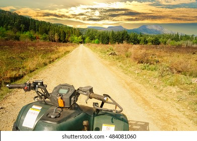Close up of the steering bar of a quad bike, ATV, in the foreground on a vanishing dirt road, forest, mountain and dramatic sky in the background, Hogsback, South Africa