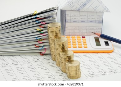 Close up step pile of gold coins and pile overload document with colorful paperclip and house with pencil and calculator have blur on finance account with white background.