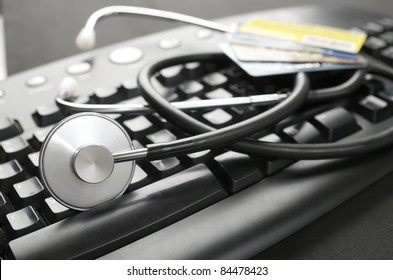 close up of a stethoscope and a computer keyboard with credit cards
